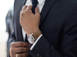ネクタイを締めるスーツ姿の男
